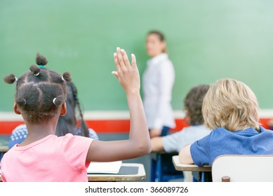Raising hand at class lesson, primary school scene. Success and education concept.