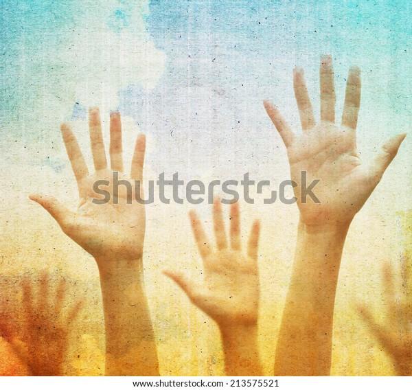 Raising hands against vintage blue sky background. Filtered image.