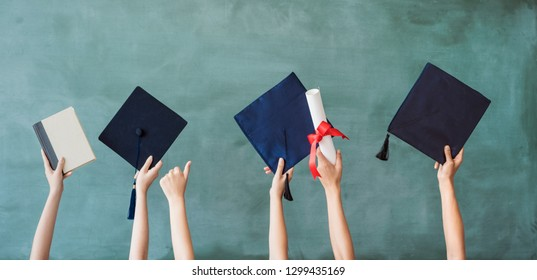 Raising hands with graduation cap on chalk board