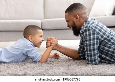 Raising A Real Man. Happy African Father And Son Arm Wrestling Competing Lying On Floor And Having Fun At Home. Little Boy Armwrestling With Daddy. Family Bond Concept. Side View