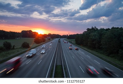 Raising red sun over German motorway with multiple cars blurred in speed motion