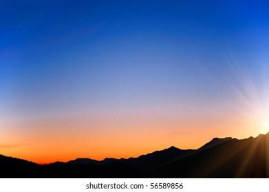 raising sun beams illuminating an  mountainside