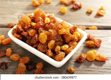Raisins in saucer on wooden table, closeup