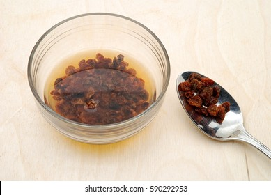 Raisins soaked in glass bowl on wooden table