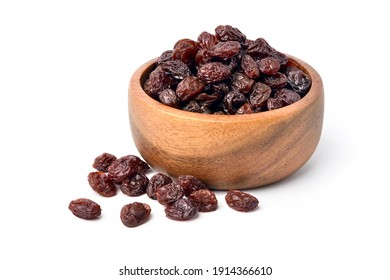 Raisins in wooden bowl isolated on white background.