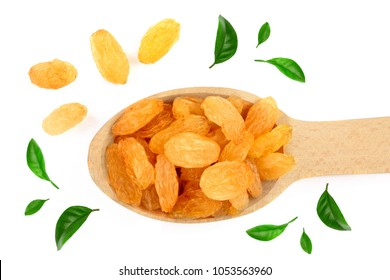 Raisins in a wooden spoon decorated with green leaves isolated on white background top view. Flat lay.