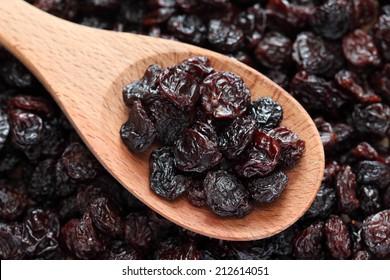 Raisins in a wooden spoon on raisins background. Close-up.