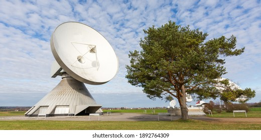 Raisting, Germany - Nov 13, 2020: Panorama with a huge satellite dish standing next to a tree.