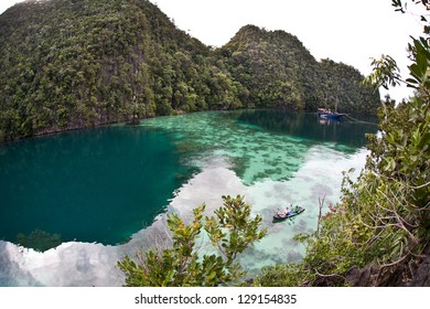 In Raja Ampat, Indonesia, an isolated lagoon is surrounded by high limestone islands covered by thick tropical vegetation.  The islands are ancient reefs uplifted millions of years ago.