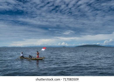 Raja Ampat, West Papua, Indonesia - August 7, 2017 : Children on small fishing boat carrying the Indonesian flag