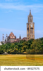 Rajabai clock tower in gothic style and green cricket field in Mumbai, Maharashtra, India