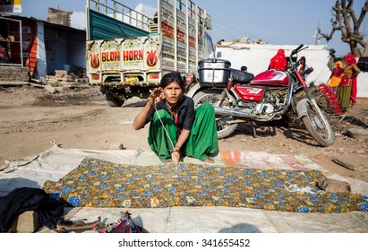 RAJASTAN, INDIA - JANUARY 9, 2015:  Woman weaves colourful textile with pattern for local market on January 9, 2015 in Jaipur, Rajastan, India
