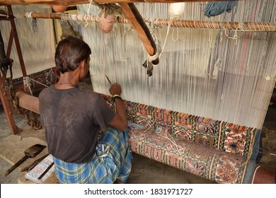 Rajasthan, India. August 24, 2017. A man weaves a handcrafted rug with an antique loom.