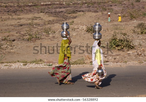 RAJASTHAN, INDIA - FEB. 21: Indian women carry water jugs on their head, Feb. 21, 2010 in Rajasthan, India.