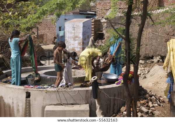RAJASTHAN, INDIA - FEB. 25: Washing day in an Indian village. Women and children wash cloth by hand in a public well on February 25, 2010 in Rajasthan, India.