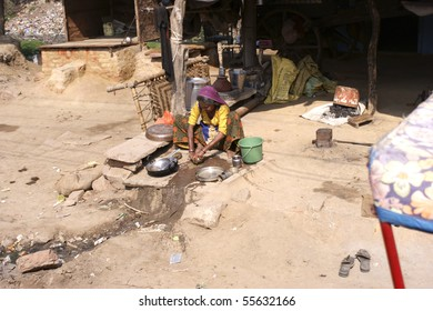 RAJASTHAN, INDIA - FEB. 26: Indian woman washing dishes on the street in front of the house at February 26, 2010 in an indian Village in Rajasthan, India.