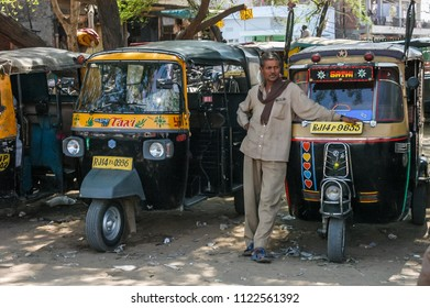 Rajasthan, India - february 21, 2006: Uniformed tuc tuc driver next to several vehicles, in the streets of a suburb of the city of Jaipur
