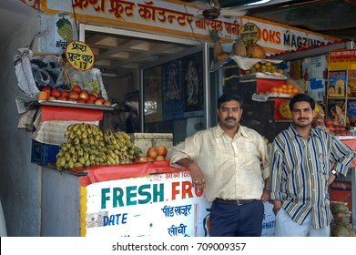 RAJASTHAN, INDIA - FEBRUARY 22, 2006: Two men pose next to their grocery store, at a road market near Jaipur