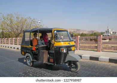 Rajasthan, India - February 25, 2006: Tuc tuc with passengers circulating on an entrance road to the city of Jaipur