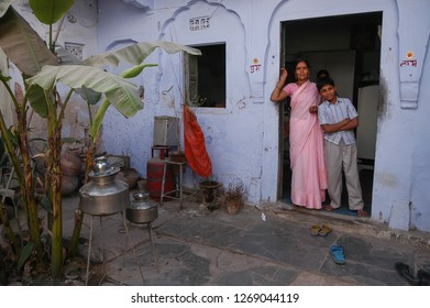 Rajasthan, India - February 25, 2006: Woman with her son in the inner courtyard of a house in a suburb of the city of Jaipur