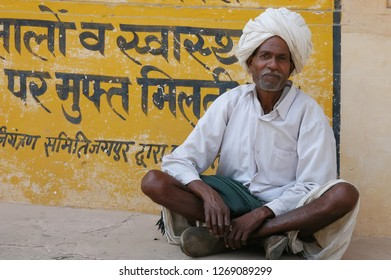 Rajasthan, India - February 25, 2006: Peasant sitting in front of a sign with texts in Sindi, on a street in the village of Naila, near Jaipur