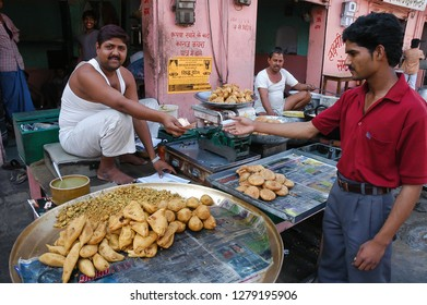 Rajasthan, India - February 25, 2006: Scene with a man paying at a food stall in a central street in the city of Jaipur
