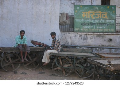 Rajasthan, India - February 25, 2006: Two workers sitting in transport cars rest, in the street of a suburb of the city of Jaipur