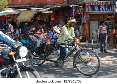 Rajasthan, India - February 25, 2006: Scene with a rickshaw transporting two passengers between the dense traffic of vehicles and people in the historic center of the city of Jaipur