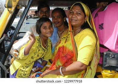 Rajasthan, India - February 26, 2006: Woman and young girls with traditional clothes, next to the driver inside a tuc tuc through the streets of the city of Jaipur