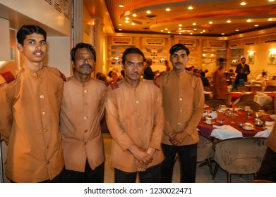 Rajasthan, India - February 26, 2006: Motion blur image of a group of waiters with uniform and blurred background of a downtown restaurant in the city of Jaipur