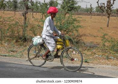 Rajasthan, India - February 26, 2006: Peasant with turban riding a bicycle next to a road full of garbage on the road to Jaipur