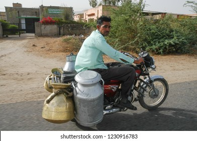 Rajasthan, India - February 26, 2006: Man delivering milk circulating on a motorcycle on the county road to Jaipur