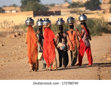 Rajasthan, India - February 27, 2013: women lugging a water pot on their head. Due to the lack of piped water, poor tribals have to fetch water from its natural sources.