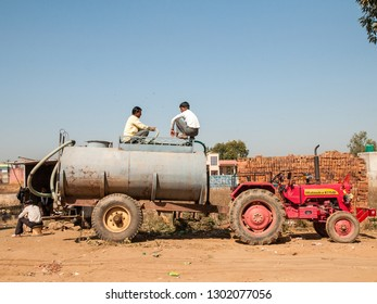 RAJASTHAN, INDIA - FEBRUARY 3, 2011: Rajasthani people in squatting position chat at a rural brickyard. Rajasthani people are known as some of the most colorful people in India.