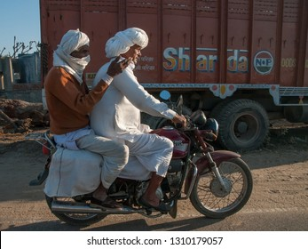 RAJASTHAN, INDIA - FEBRUARY 3, 2011: Motorbiker with passenger in the countryside of Rajasthan. Rajasthan is the largest Indian state by area.