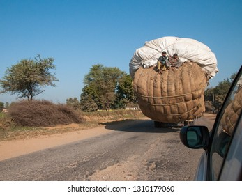 RAJASTHAN, INDIA - FEBRUARY 3, 2011: Loaded truck with passengers on a country road in Rajasthan. Trucks carrying heavy loads characterize traffic in India.