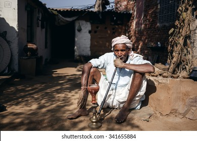 RAJASTHAN, INDIA - JANUARY 9, 2015: Old Indian man smoking hookah on January 9, 2015 in Rajasthan, India