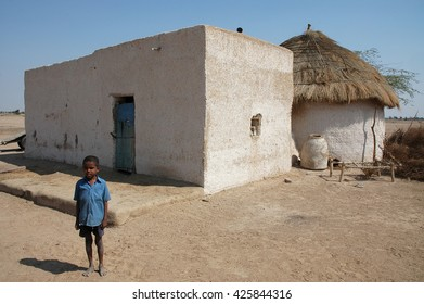 RAJASTHAN, INDIA - MARCH 03, 2006: Young Indian at the door of his house in northern Rajasthan