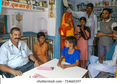 RAJASTHAN, INDIA - MARCH 08, 2006: Rural doctor surrounded by patients, in his consultation in the village of Nayla Fort