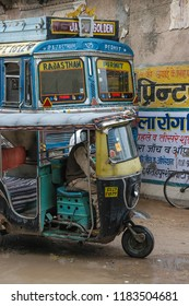 Rajasthan, India - march 10, 2006: Detail of the front of a tuc-tuc circulating on a street in the town of Fatehpur, with a public transport bus in the background