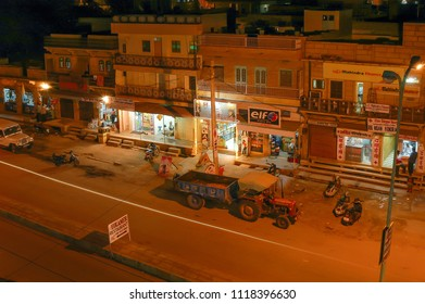 Rajasthan, India - march 12, 2006: Night view of the street of a neighborhood in the city of Jaisalmer, with a tractor parked next to the shops and restaurants in the area