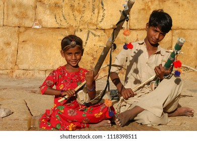 Rajasthan, India - march 12, 2006: A couple of children playing musical instruments in a street, near the walls of the historic city of Jaisalmer