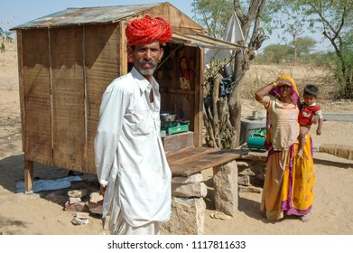 Rajasthan, India -march 13, 2006: Family of rajasthani farmers next to a small shop on the road to the city of Jodhpur