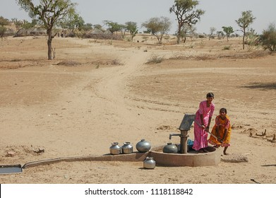 Rajasthan, India - march 13, 2006: Two girls pumping water at a water well near a village in the desert region of Jaisalmer