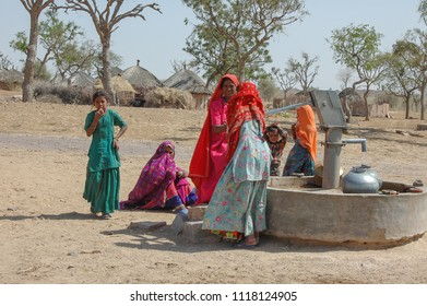 Rajasthan, India - march 13, 2006: Group of women and children around a water well, in the desert region of Jaisalmer, in the north of the country