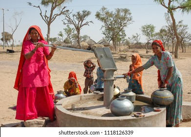 Rajasthan, India - march 13, 2006: Two women with children around, pumping water to fill the metal pots in a well, in the desert region of Jaisalmer, in the north of the country