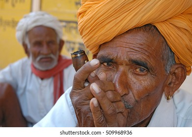 RAJASTHAN, INDIA - MARCH 14, 2006: Old man smoking a traditional pipe in the region of Naila
