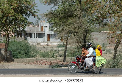 RAJASTHAN, INDIA - MARCH 14, 2006: Family with children, on board a motorcycle, traveling on a road in the region