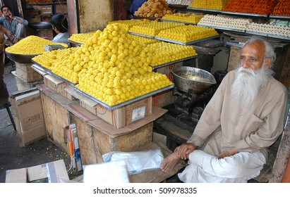 RAJASTHAN, INDIA - MARCH 14, 2006: Old salesman, in his stall selling sweets, on a street in Jaipur
