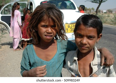 RAJASTHAN, INDIA - MARCH 14, 2006: Groups of children, curious approach taxis which stop on the road
